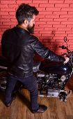 Man with beard, biker in leather jacket near motor bike in garage, brick wall background. Masculine hobby concept. Hipster, brutal biker in leather jacket sits down on motorcycle, rear view. poster