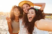 Three positive multiethnic women 20s in summer clothing smiling at camera while taking selfie photo during holiday on nature poster