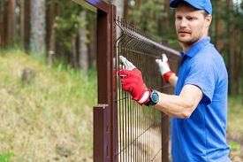 Worker Installing Brown Welded Metal Mesh Fence