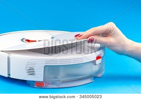 Robot Vacuum Cleaner Isolated On Blue Background. Opening The Lid To Replace Or Clean The Garbage Co