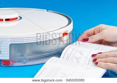 Robot Vacuum Cleaner Isolated On Blue Background, Reading Instructions. Close Up Photo