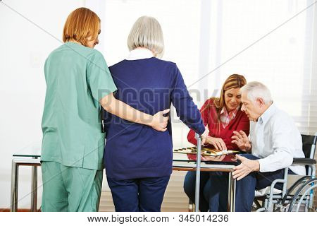 Woman nursing elderly people in retirement home