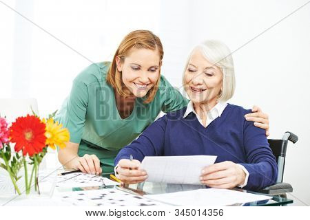 Senior makes memory training in nursing home and shows solution of a nurse