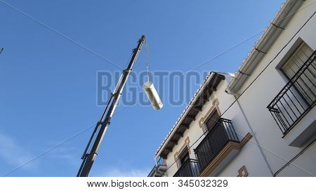 Alora, Spain - November 9, 2019: Large Mobile Crane Hoisting Solar Hot Water Container Over Rooftop