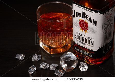 St.Petersburg, Russia - December 2019 - Bottle of Jim Beam bourbon whiskey and glass with drink and ice  on wooden table on brown background. Kentucky straight bourbon whiskey