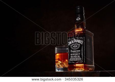 St.Petersburg, Russia - December 2019 - Bottle of Jack Daniel's whiskey and glass with drink and ice  on wooden table on brown background with copy space. Brand of the American whiskey