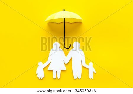 Health Insurance Concept. Family Cutout Under Umbrella On Yellow Background Top-down Copy Space