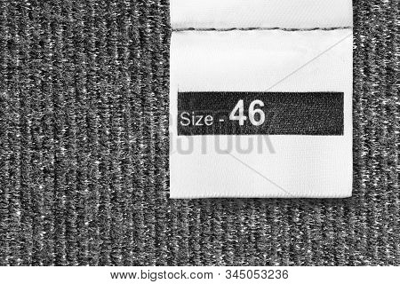 46 Size Clothes Label On Black Knitted Textile Background Closeup