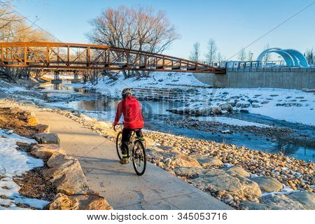 male cyclist is riding a bike in winter sunset scenery - Poudre River Trail in Fort Collins, Colorado at downtown whitewater park, recreation and commuting concept