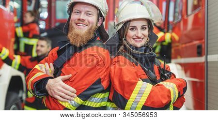 Fire fighter man and woman standing together shoulder to shoulder