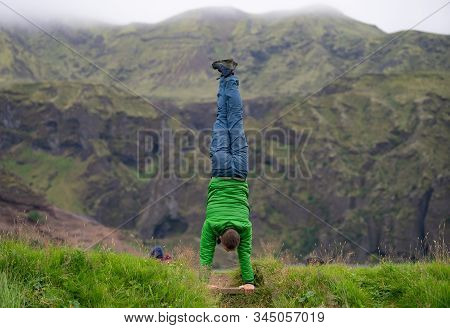 Young Guy Standing On His Hands With Fogy Mountain Background On The Way Of Laugavegur Trail, Icelan