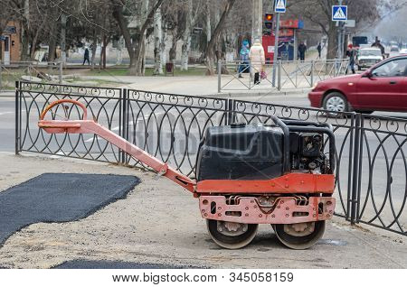 Manual Compact Paver On The Sidewalk Behind The Fence. Сompact Asphalt Roller. Manual Compact Paver.