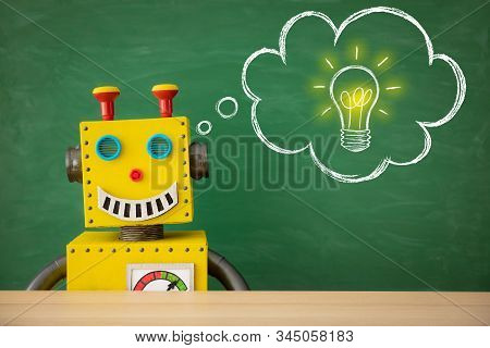 Funny Toy Robot Teacher Against Chalkboard With Copy Space In Class. Innovation Technology In School