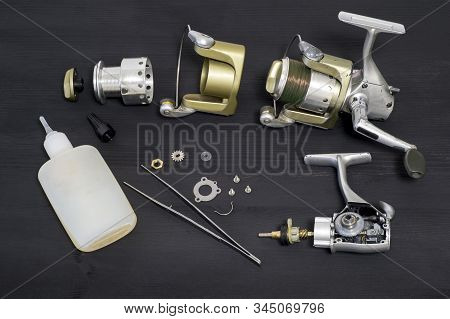 A Fishing Spinning Reel As A Whole And A Second Similar Completely Disassembled On A Dark Wooden Bac