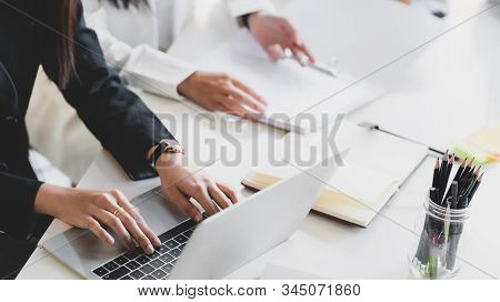 Close Up View Of Young Businessman Typing On Laptop While Siting In Meeting Room With Co Worker And