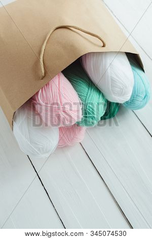 Oval Acrylic Colorful Wool Yarn Thread Skeins Lying In Kraft Paper Brown Package On White Wooden Boa