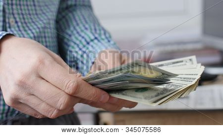 Male Hands Count Cash Money In The Office. Close Up Of Man Hands Count Dollar Bills. Starting Invest