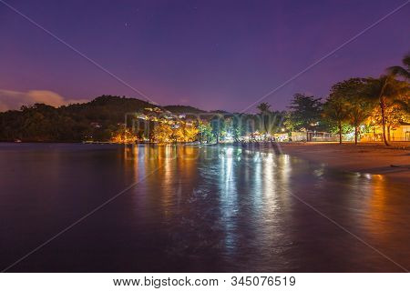 Landscape View Of Anse A L'ane Sandy Beach With Palm Trees And Calm Bay At Colorful Dusk With Peacef