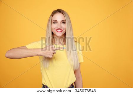 Happy Woman Model In The Yellow T-shurt With Red Lips Pointing To The Side Isolated.