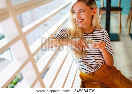 Beautiful Woman Enjoying A Cup Of Coffee While Relaxing At Home.