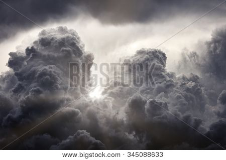 Sun Rays Breaking Through The Dark Clouds. Clouds Background. Dramatic Grey Clouds.