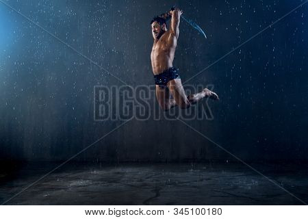 Side View Of Angry Tensed Wet Roman Gladiator Holding Blade. Muscular Agressive Shirtless Warrior In