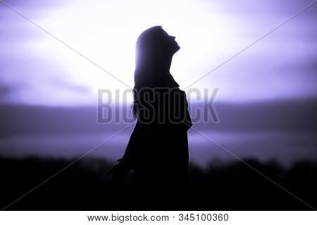 Youth Woman Soul At Purple Sun Meditation Awaiting Future Times. Silhouette In Front Of Sunset Or Su