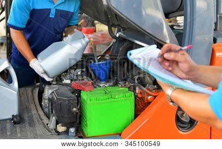 The Mechanic Is Checking The Quality And Refueling And Pouring Oil Quality Into The Engine Motor Tra