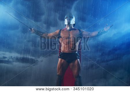 Front View Of Wet Roman Gladiator In Iron Helmet And Red Cloak Holding Sword. Muscular Shirtless Spa