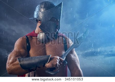 Front View Of Wet Roman Gladiator In Iron Helmet And Red Cloak Looking Ar Raindrops On Sword. Muscul