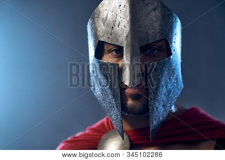 Portrait Of Spartan Warrior Standing And Looking At Camera. Close Up Of Mature Man In Red Cloak And
