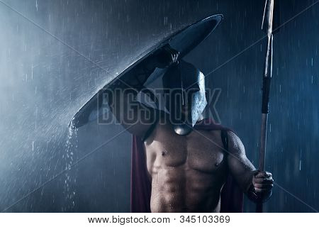 Front View Of Fearless Muscular Spartan Hiding From Rain With Shield. Portrait Of Ancient Warrior In