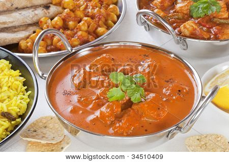 Selection of curry dishes with rogan josh pillau ricechana dhalchicken jalfrezi and poppadums. poster