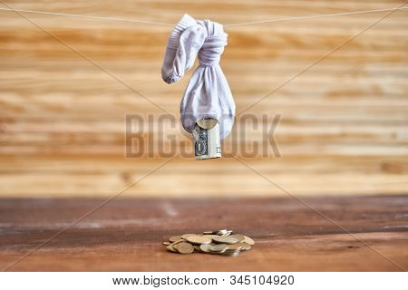 An Old Leaky Sock Hanging On A Rope. From The Hole Drops The Dollar And The Euro. Economy Concept
