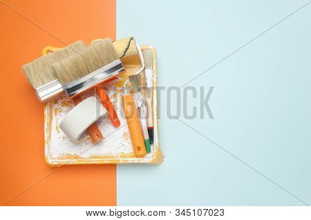 Set Of Tools For Painting: Paint Brushes, Masking Tape, Paint Roller On Orange And Blue Background.