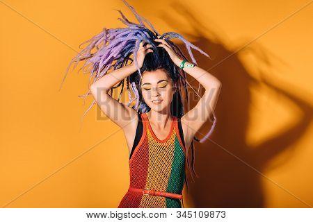 Hipster Woman Wearing In Rasta Dress And A Rasta Color Make-up Is Dancing To Reggae Music. Orange Ba