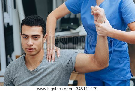 Athlete Of Mixed Races With A Shoulder Injury In A Rehabilitation Center. Physiotherapist Helps Reco