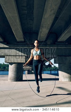 Young Sporty Woman Exercising With Skipping Rope Outdoors. Cardio And Fitness Workout