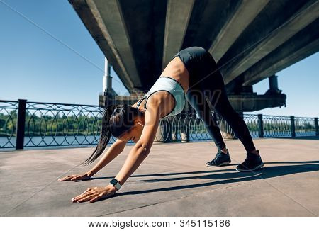 Young Sporty Woman Doing Yoga Asana Downward Facing Dog Under Industrial Bridge. Adho Mukha Shvanasa