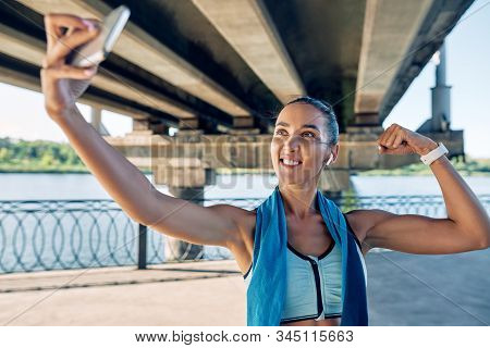 Beautiful Sporty Woman Making Selfie Flexing Her Muscles. Sport Concept