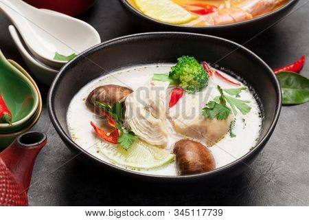 Tom Yum and Tom Kha traditional Thai soups with seafood, chicken, mushrooms, coconut milk and hot spices. With green tea pot and bowl