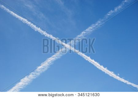 Contrails In Blue Sky. White Cross Made Of Steam Traces From Planes
