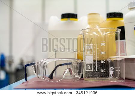 Clear Plastic Protection Goggles Next To Empty Glass And Plastic Containers In A Science Lab