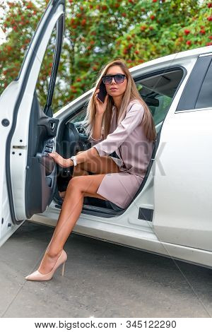 Beautiful Girl Gets Out White Business Car Sedan. Calls Smartphone, Important Negotiations, Listens