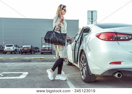Girl In Autumn In City Parking Lot, In Summer Car. He Opens Door Takes Out Removes Shopping Bag. Whi