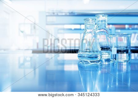 Clear Water In Beaker And Flask Glass In Chemistry Blue Science Laboratory Background