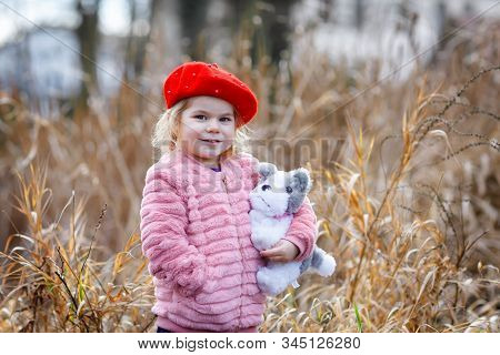 Outdoor Portrait Of Little Cute Toddler Girl In Pink Coat And Red Fashion Hat Barret Playing With So