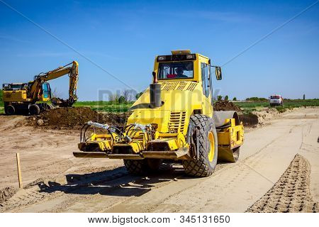 Vibration Plate Compactor Is Mounted To The Steamroller, Compacting Sand At Road Construction Site.