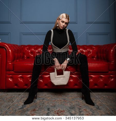 Glamorous Young Woman In Trendy Black Clothes With A Stylish Pearl Bag In A Vintage Pearl Top Is Sit