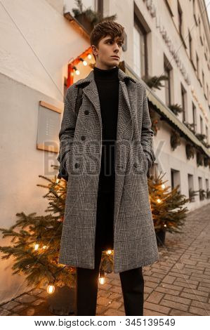 Handsome Pretty Young Man In A Elegant Gray Checkered Coat Is Standing Near The Building Between Two